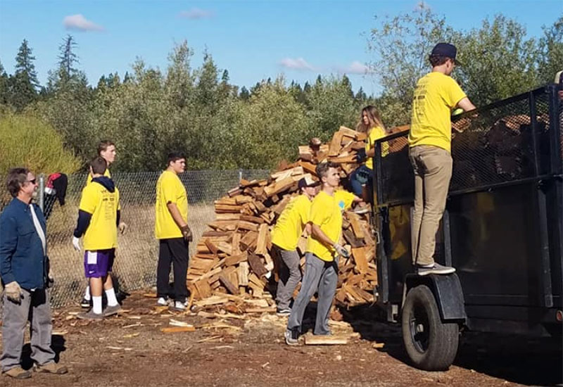 Volunteers moving firewood